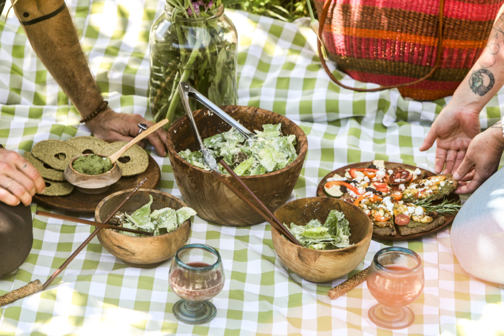 Assortment of plant based foods set out on a table cloth on the ground for a picnic